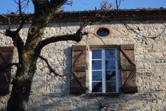 Venster met open houten blinden onder het dak van een oud steenhuis royalty-vrije stock afbeeldingen