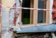 Venster op oude gebroken muur met zichtbare bakstenen achter de rode en witte waarschuwingsband Royalty-vrije Stock Afbeeldingen