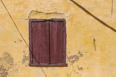 Venster van een oud huis met een gesloten blind stock afbeelding