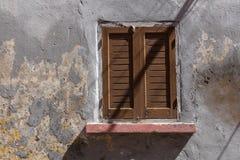 Venster van een oud huis met een gesloten blind stock afbeeldingen