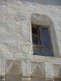 Venster van een wit oud gebouw met sommige graven schetsen in de muur in het dorp van Mustafapasa in Cappadocia Turkije royalty-vrije stock afbeeldingen