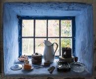 Vensterbankstilleven met uitstekende die voorwerpen door blauwe muren worden ontworpen stock foto's