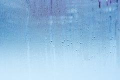 Vensterglas met condensatie, hoge vochtigheid in de ruimte, grote waterdruppeltjes, koude toon stock foto's