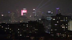 Vensters en dak van een huis met meerdere verdiepingen bij nacht Ingeschakeld en van het licht Opvlammende lichten in de vensters stock videobeelden