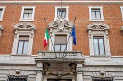 Vensters en deuren op de oude historische bouw van een handelsbank met beeldhouwwerken en ornamenten in Rome waarop de vlag hang Royalty-vrije Stock Afbeelding