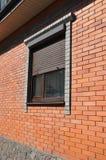Vensters met rollend blind op de nieuwe buitenkant van de de bouwvoorgevel van het baksteenhuis royalty-vrije stock fotografie