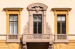 Vensters op een rij en balkon op voorgevel van de bureaubouw Stock Afbeeldingen