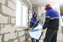 Venstersinstallatie Twee bouwvakkers die glas installeren royalty-vrije stock afbeelding