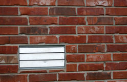 Vent on brick house. A silver vent on a red brick house Royalty Free Stock Image