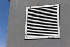 Vent window on gray concrete wall Stock Image