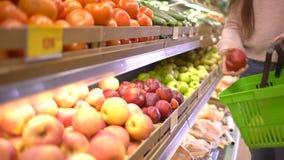 Venta, compras, comida, consumerismo y concepto de la gente - mujer con las manzanas de compra del bolso en el colmado almacen de video
