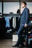 Venta, compras, moda, estilo y concepto de la gente - hombre joven elegante en un soporte y las esperas de la capa para las mucha fotografía de archivo libre de regalías