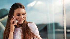Venta, consumerismo: Mujer joven con los smartphones y los panieres que se colocan y que hablan cerca de centro comercial metrajes