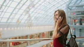 Venta, consumerismo: Mujer joven con los smartphones y los panieres que se colocan y que hablan cerca de centro comercial almacen de metraje de vídeo