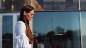 Venta, consumerismo: Mujer joven con smartphones y panieres que camina y que habla cerca de centro comercial almacen de video