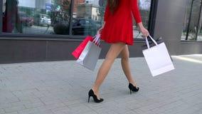 Venta, consumerismo: Señora confiada en los talones con los panieres que camina después en una ciudad Piernas femeninas hermosas almacen de video