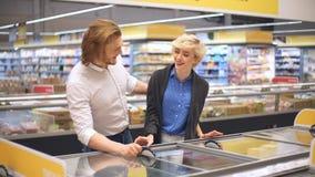 Venta, consumerismo y concepto de la gente - par feliz con la comida congelada de compra del carro de la compra en el colmado o almacen de metraje de vídeo