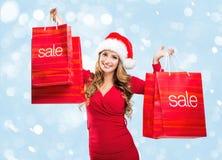 VENTA de la Navidad - la mujer que lleva a cabo una venta del rojo empaqueta Fotos de archivo libres de regalías