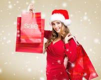 VENTA de la Navidad - la mujer que lleva a cabo una venta del rojo empaqueta Foto de archivo libre de regalías