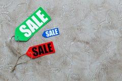 Venta del invierno Redacte la venta en etiquetas coloridas en copyspace de piedra gris de la opinión superior del fondo Fotos de archivo