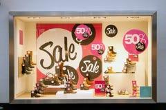 Venta en la ventana de la tienda de la zapatería Imagen de archivo libre de regalías
