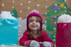 Venta, la Navidad, días de fiesta y concepto de la gente - bebé sonriente en vestido rojo con los bolsos Fotografía de archivo libre de regalías