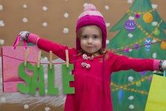 Venta, la Navidad, días de fiesta y concepto de la gente - el bebé sonriente en vestido rojo con venta firma y los bolsos Imagenes de archivo