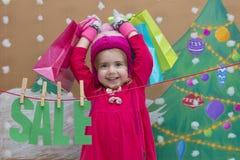 Venta, la Navidad, días de fiesta y concepto de la gente - el bebé sonriente en vestido rojo con venta firma y los bolsos Fotografía de archivo libre de regalías
