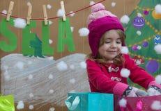 Venta, la Navidad, días de fiesta y concepto de la gente - el bebé sonriente en vestido rojo con venta firma y los bolsos Imágenes de archivo libres de regalías