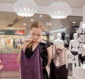 Venta, moda, consumerismo y concepto de la gente - mujer joven feliz que elige la ropa en tienda de la alameda o de ropa Imagen de archivo libre de regalías