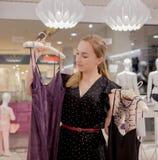 Venta, moda, consumerismo y concepto de la gente - mujer joven feliz que elige la ropa en tienda de la alameda o de ropa Foto de archivo libre de regalías