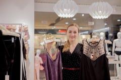 Venta, moda, consumerismo y concepto de la gente - mujer joven feliz que elige la ropa en tienda de la alameda o de ropa Imagen de archivo