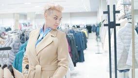 Venta, moda, consumerismo y concepto de la gente - panieres de la mujer que eligen la ropa en tienda de la alameda o de ropa almacen de metraje de vídeo