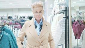 Venta, moda, consumerismo y concepto de la gente - panieres de la mujer que eligen la ropa en tienda de la alameda o de ropa metrajes