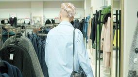 Venta, moda, consumerismo y concepto de la gente - panieres de la mujer que eligen la ropa en tienda de la alameda o de ropa almacen de video