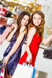 Venta, turismo, compras y concepto feliz de la gente - dos mujeres hermosas con los panieres en el centro comercial Foto de archivo libre de regalías