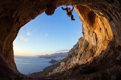 Ventaja del hombre joven que sube en techo en cueva Fotografía de archivo libre de regalías