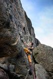 Ventaja del hombre joven que sube una roca, equipo que sube que lleva, al aire libre imagen de archivo