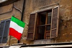 Ventana abierta con la bandera italiana en fachada en Roma, Italia Foto de archivo libre de regalías