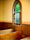 Ventana al lado de los bancos en iglesia vieja simple Fotos de archivo libres de regalías