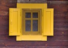 Ventana amarilla en la pared de madera Fotos de archivo