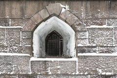 Ventana antigua en la pared gruesa de la fortaleza en invierno en la nieve Foto de archivo libre de regalías