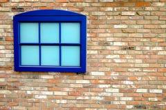 Ventana azul en la pared hecha de ladrillos Foto de archivo