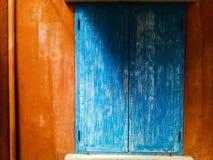 Ventana azul y pared anaranjada con la luz del sol y la sombra suave Imagen de archivo