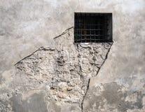 Ventana barrada en pared erosionada Foto de archivo libre de regalías