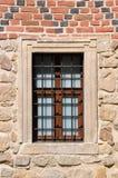 Ventana barrada en una pared de ladrillo roja Imagen de archivo libre de regalías