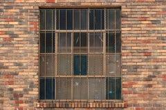 Ventana barrada fachada del ladrillo rojo Imagen de archivo libre de regalías
