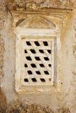 Ventana barrada piedra en la pared de piedra Imágenes de archivo libres de regalías