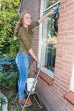 Ventana casera que se lava del adolescente holandés afuera Foto de archivo