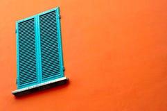 Ventana cerrada en la pared anaranjada Fotos de archivo libres de regalías